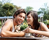 Young Couple Sit Close to Each Other at a Table Outdoors, Laughing