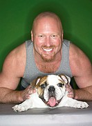 Studio Portrait of a Muscular Man and His Bulldog
