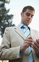 Businessman Standing Outside Using His Handheld PC