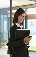 Portrait of a Female Estate Agents Standing Holding a Folder and Mobile Phone