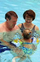 Senior couple swimming with toddler