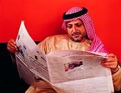 Arab man reading Arabic newspaper