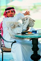 Arab businessman screwing up newspaper in anger