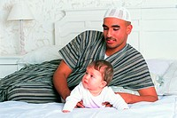 Father and toddler on bed