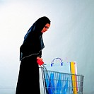 Arab woman pushing a shopping trolley