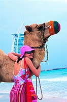 Western tourist hugging a camel on the beach in Dubai, United Arab Emirates