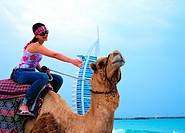 Western woman riding a camel on the beach in Dubai, United Arab Emirates