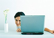 Woman peeking around side of laptop