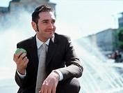 Geschaeftsmann sitzt an einem Brunnen mit einem Apfel in der Hand - Mittagspause , Businessman sitting at the Edge of a Fountain with an Apple in his ...