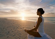 Young Woman Sits on the Beach by the Sea, Meditating in the Lotus Position at Sunrise