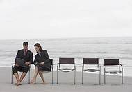Businessman and Businesswoman Sit at the End of a Row of Chairs on a Beach, Using a Laptop