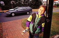 Six year old boy leans on porch post. USA