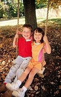 Six year old boy and girl are all smiles as they swing together
