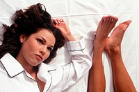 young couple in bed relaxing, foot detail