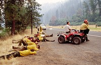 Firemen rest by roadside after a night of fighting forest fires. Idaho, USA