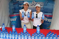 Hispanic women showing free Propel bottled fitness water. Sport and Fitness Festival. Lummus Park. Miami Beach. Florida. USA.
