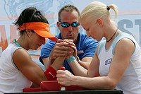 Female arm wrestlers, male judge starts competition. Sport and Fitness Festival. Lummus Park. Miami Beach. Florida. USA.
