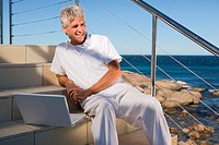 Mature man with laptop by the sea