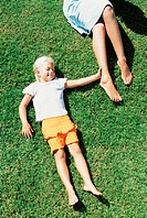 Mother and daughter lying on lawn (thumbnail)