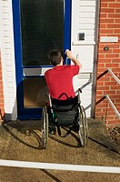 Disabled man opening his front door