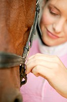 Young woman adjusting horse's bridle