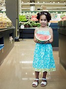 Portrait of girl with watermelon in grocery store