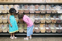 Two girls at bulk bins in grocery store