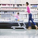 Blurry woman with daughter in grocery cart