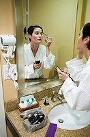 Woman in bathrobe applying makeup