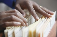 Close up of hands sorting through files