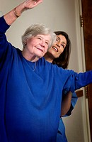 Nurse helping senior woman with exercising