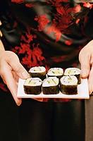 Hands serving maki-sushi