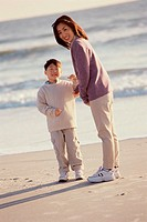Portrait of a mother and her son standing on the beach