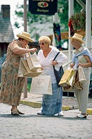 Three senior women walking with shopping bags