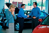 Mid adult woman looking at a car in a car showroom