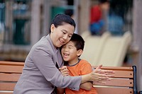 Mother hugging her son sitting on a park bench (thumbnail)