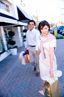 Mid adult couple carrying shopping bags