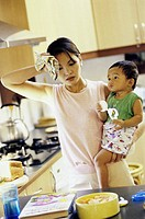 Mother carrying her son in the kitchen
