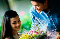 Young man giving a bouquet to young woman
