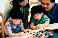 Parents watching their two sons coloring with crayons