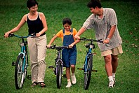 Parents with their daughter walking with bicycles in a park
