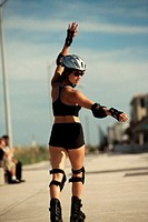 Rear view of a young woman inline skating on a road