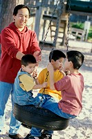 Father playing with his three sons on a swing