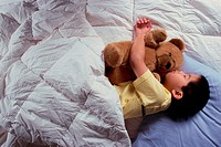 Boy sleeping with a teddy bear