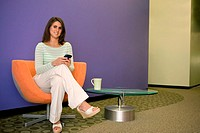 Portrait of a businesswoman sitting in an office holding a palmtop (thumbnail)