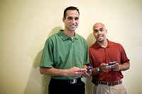 Portrait of two businessmen standing in an office holding palmtops