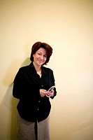Portrait of a businesswoman standing in an office holding a mobile phone