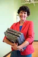 Portrait of a businesswoman carrying three laptops