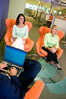 High angle view of two businesswomen sitting on chairs with a businessman sitting in front of them