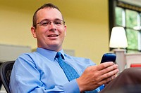 Portrait of a businessman sitting in an office holding a palmtop
